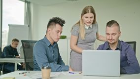 People Group Using Laptop in Modern Startup Office. Creative business team meeting in modern start up office female team leader pointing at screen discussing Stock Image