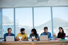 Creative business team sitting in a row and working together on table Stock Images