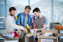 Creative business team sorting clothes in donation box Stock Photo