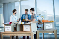 Creative business team sorting clothes in donation box Stock Image
