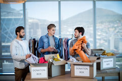 Creative business team sorting clothes in donation box Royalty Free Stock Image