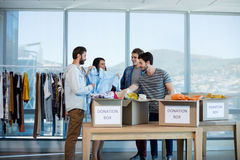 Creative business team sorting clothes in donation box Royalty Free Stock Images