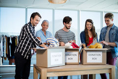 Creative business team sorting clothes in donation box Royalty Free Stock Photos