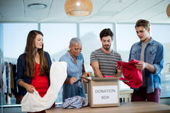 Creative business team sorting clothes in donation box Stock Images