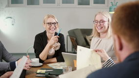 Creative business team at the table in startup office happy beautiful blonde women are involved in the conversation. Close up of Creative business team sitting stock footage