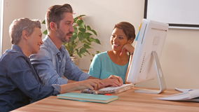Creative business team using computer and looking at camera stock footage