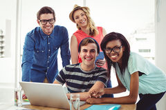 Creative business team working hard together on laptop Royalty Free Stock Photo