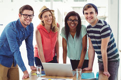 Creative business team working hard together on laptop Royalty Free Stock Image
