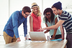 Creative business team working hard together on laptop Stock Image