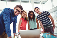 Creative business team working hard together on laptop Royalty Free Stock Photos