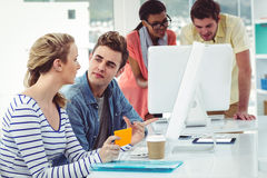 Creative business team working hard together on pc Royalty Free Stock Images