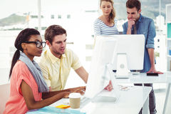 Creative business team working hard together on pc Royalty Free Stock Photos