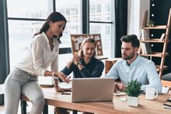 Creative business team. Young modern woman in smart casual wear. Creative business team. Young modern women in smart casual wear pointing at laptop while working stock images
