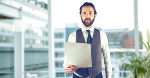 Creative businessman holding paper while standing in office against defocused buildings. Digital composite of Creative businessman holding paper while standing Stock Photo