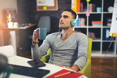 Creative businessman listening music at desk in office. Businessman listening music at desk in office Stock Photography