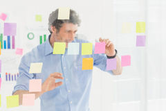 Creative businessman looking at post-it Stock Photo