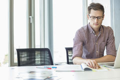 Creative businessman reading file at desk in office Stock Photography