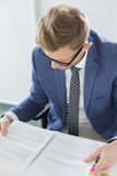 Creative businessman reading file at desk in office Royalty Free Stock Photo