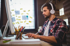 Creative businessman using computer while listening music. At desk in office Stock Photos