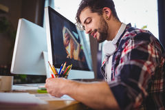 Creative businessman working at computer desk in office Stock Images