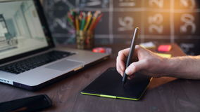Creative businessman writing on graphic tablet while using laptop in office stock footage