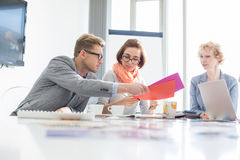 Creative businesspeople analyzing documents at desk in office Stock Image
