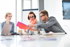 Creative businesspeople analyzing documents at desk in office Stock Photo