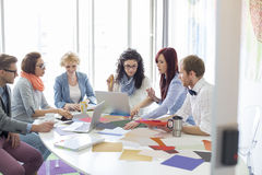 Creative businesspeople analyzing photographs at conference table in office Stock Images