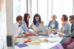 Creative businesspeople analyzing photographs at conference table in office royalty free stock image