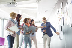 Creative businesspeople discussing over documents on wall in office stock images