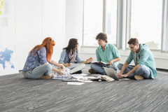Creative businesspeople discussing while sitting on floor in office Stock Photography
