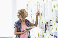 Creative businesswoman analyzing papers stuck on wall in office Royalty Free Stock Images