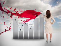 Creative businesswoman drawing a chart next to red paint splash Stock Image