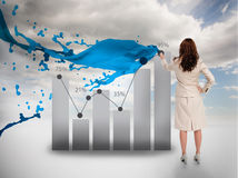 Creative businesswoman drawing a chart with paint splash. And blue sky on the background stock images