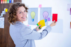 Creative businesswoman holding color cards and looking at camera Stock Photos