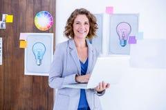 Creative businesswoman holding laptop computer Stock Image