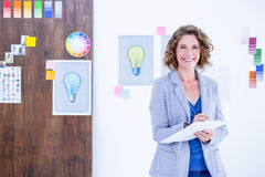 Creative businesswoman looking at camera and taking notes Stock Photography