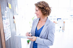 Creative businesswoman looking at pictures and taking notes Stock Photo