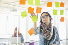 Creative businesswoman reading sticky notes on glass wall with colleague working in background at office Stock Images