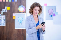 Creative businesswoman using her smartphone Royalty Free Stock Image