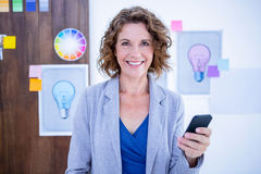 Creative businesswoman using her smartphone Royalty Free Stock Photography
