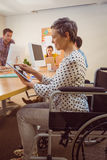 Creative businesswoman in wheelchair using a tablet Royalty Free Stock Images