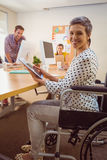 Creative businesswoman in wheelchair using a tablet Stock Photos
