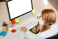 Creative businesswoman working at computer desk Stock Photo
