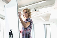 Creative businesswoman writing on presentation board in office Royalty Free Stock Images