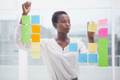 Creative businesswoman writing on sticky notes on window Stock Image