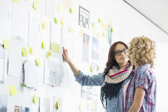 Creative businesswomen discussing over papers stuck on wall in office stock photo
