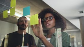 Creative businesswomen planning, brainstorming with adhesive notes. Portrait of attractive businesswoman brainstorming with her colleague, using adhesive notes stock video footage