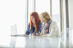 Creative businesswomen working on laptop together in office Royalty Free Stock Photos