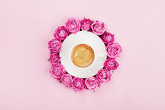 Creative card with coffee cup and beautiful pink rose flowers on pastel background top view in flat lay style. Fashion breakfast. royalty free stock images